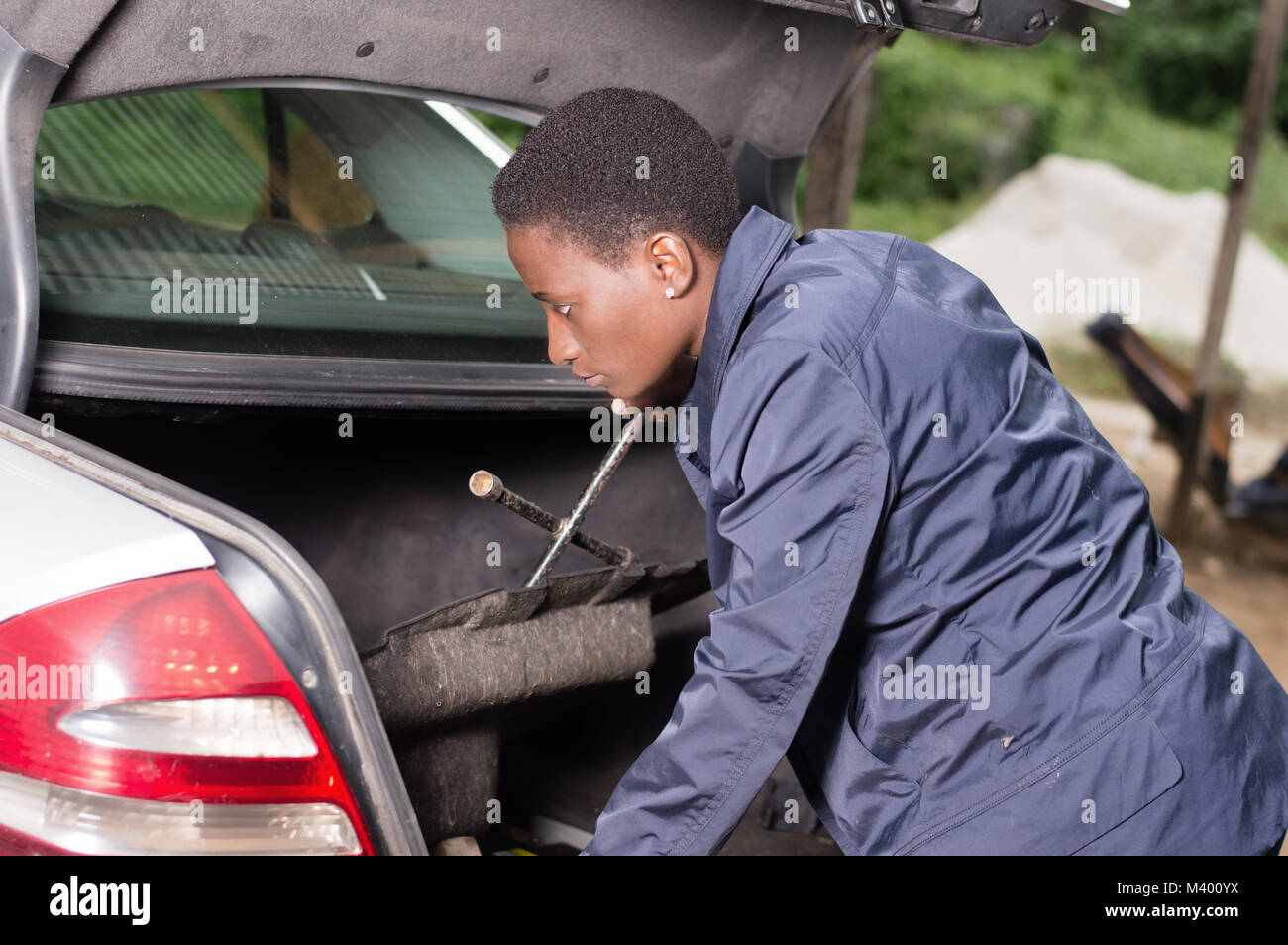 A smiling mechanic looks for her work tools in the back of a car in the garage. - Stock Image