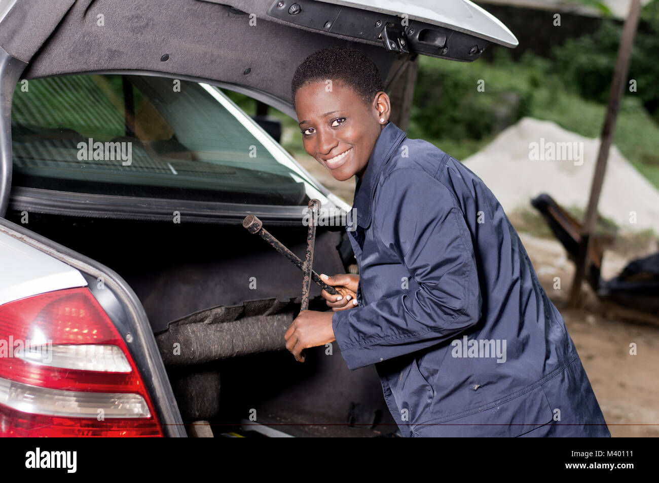 Young smiling mechanic takes her tool from the back of a car in the garage. - Stock Image
