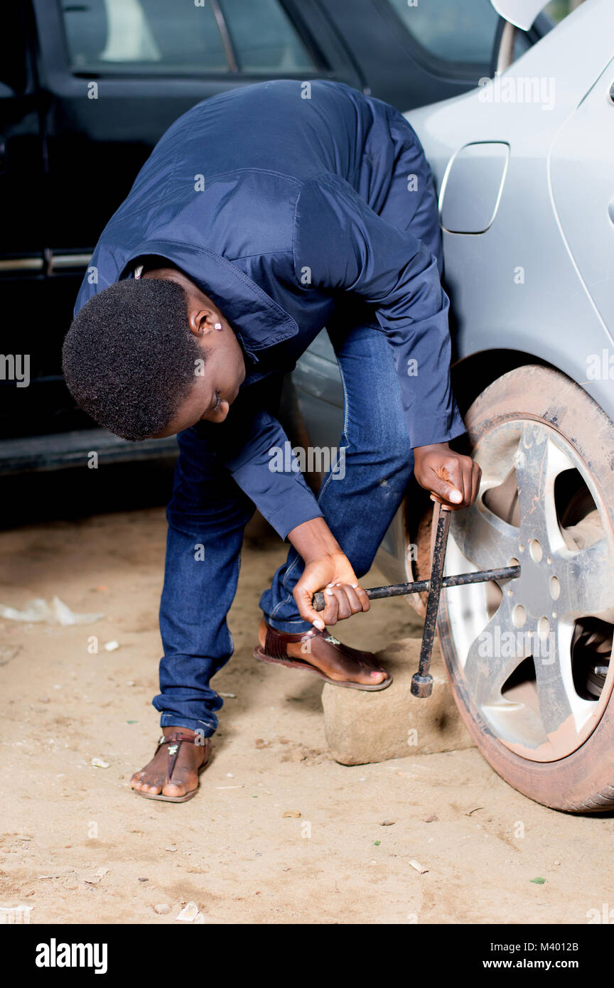 Young mechanic removing the wheel of a car in a workshop. - Stock Image