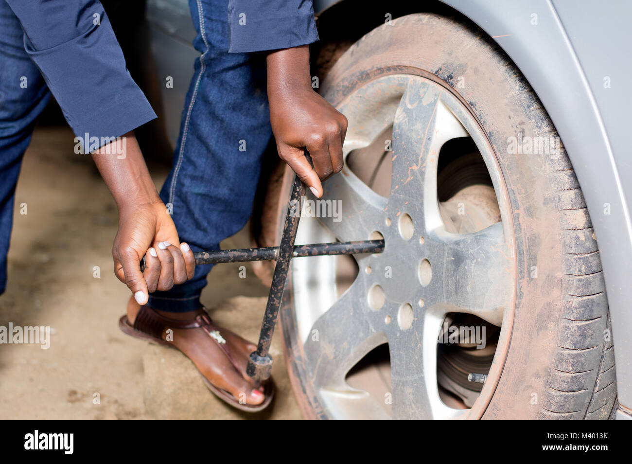Closeup  of mechanic's arms remove the tire of a car in workshop - Stock Image
