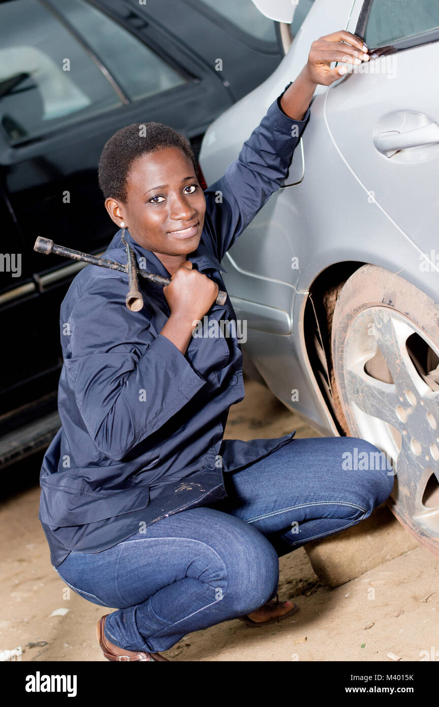 Young smiling mechanic squatting near the tire of a car she is preparing to remove. - Stock Image