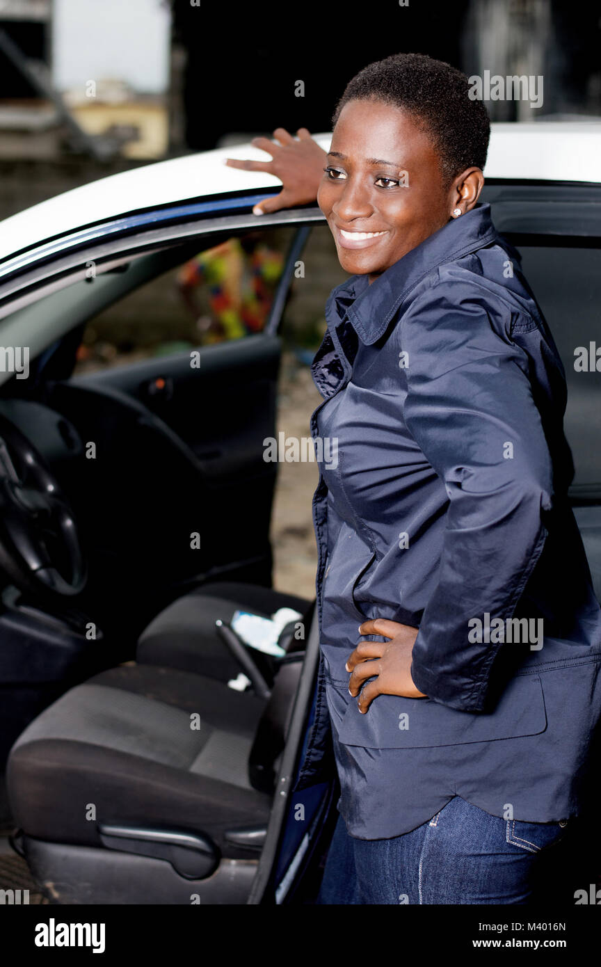 Young female mechanic standing beside this car is happy to settle the breakdown. - Stock Image