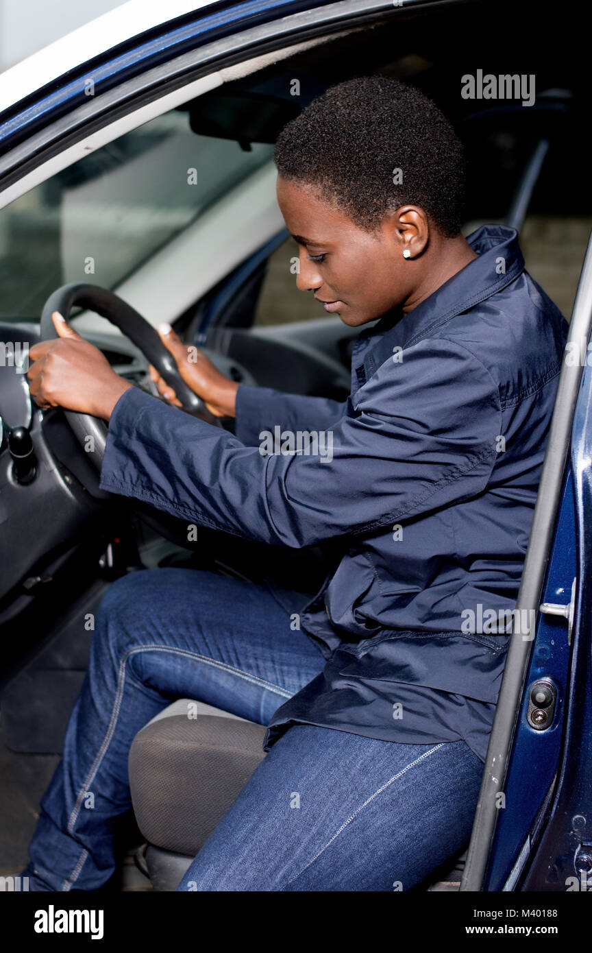 Young female mechanic seated at the wheel of this car controls its various pedals - Stock Image