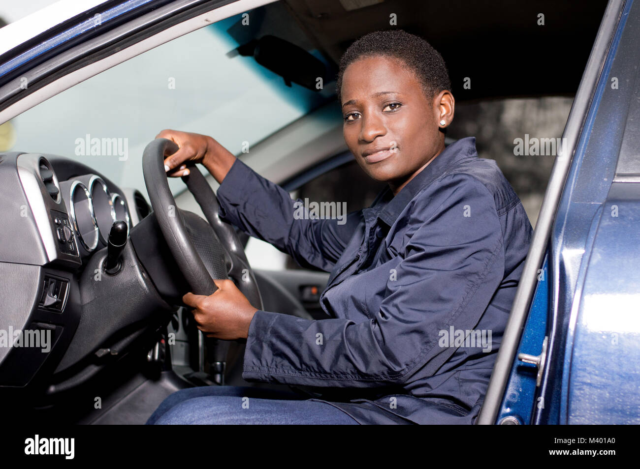 Beautiful young woman sitting at the wheel and looking at the camera - Stock Image