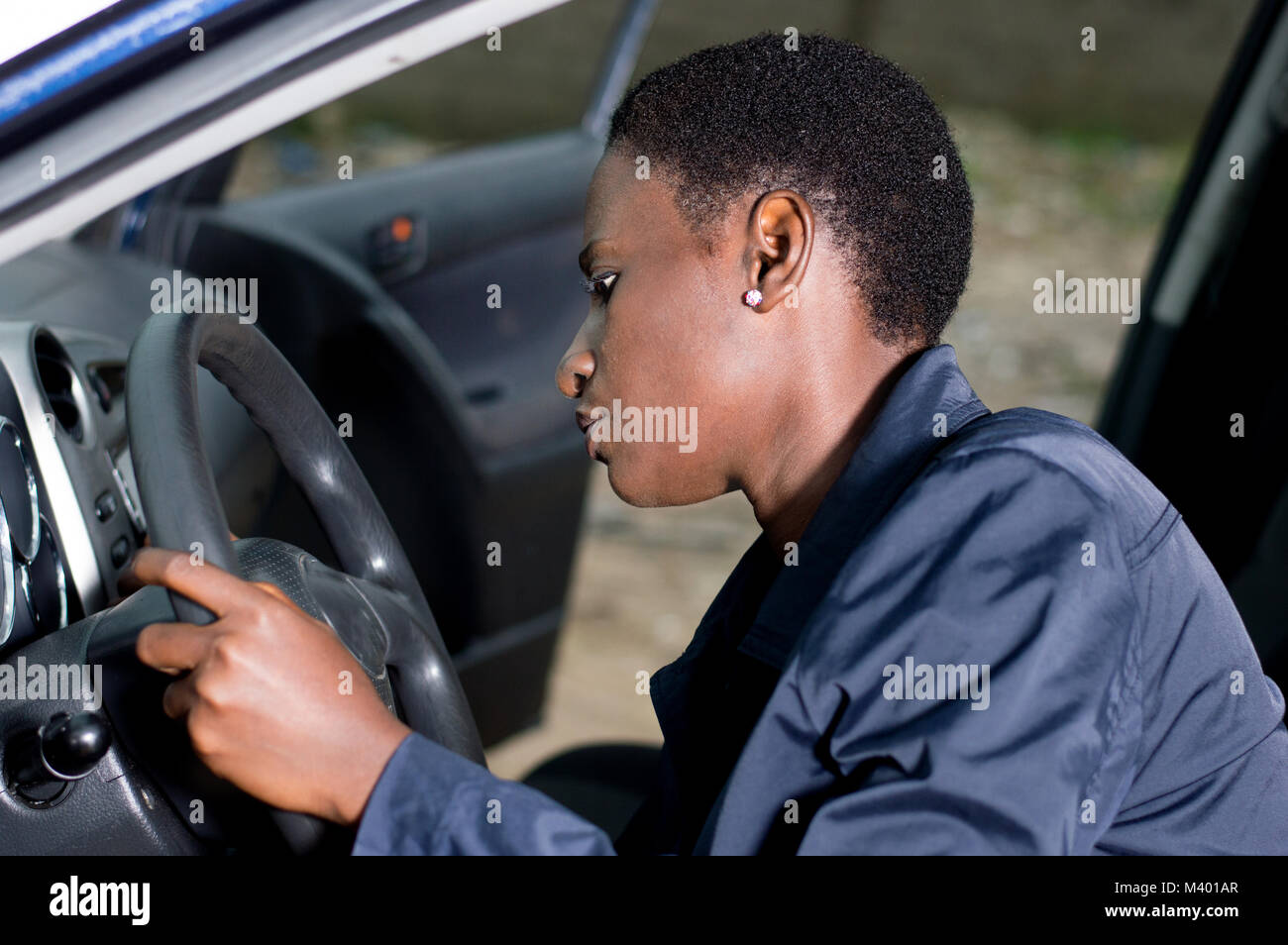 A young mechanic sitting at the wheel of a car, checks her ignition. - Stock Image