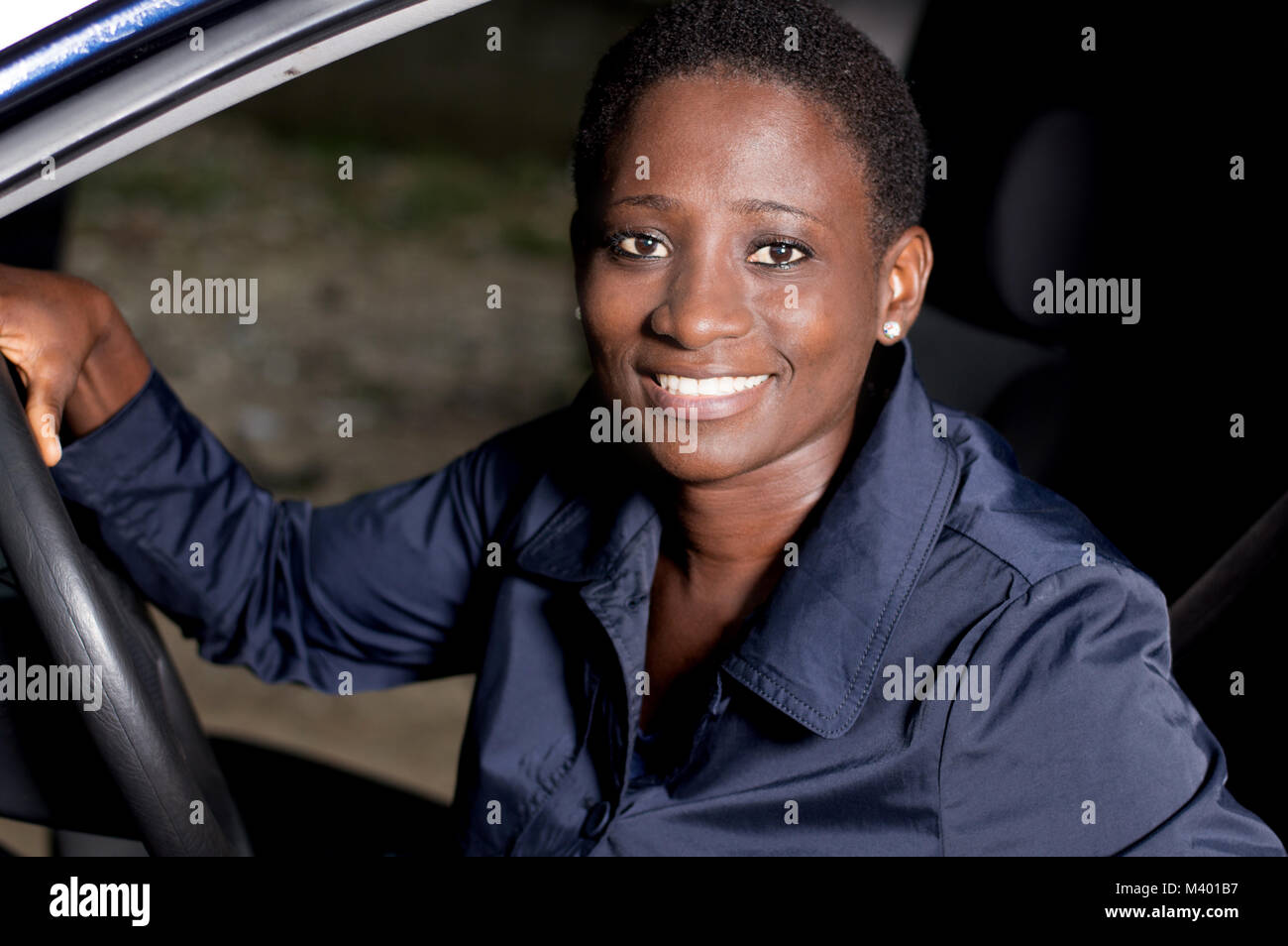 Young woman sitting in a car, hands on the steering wheel smiling at the camera. - Stock Image