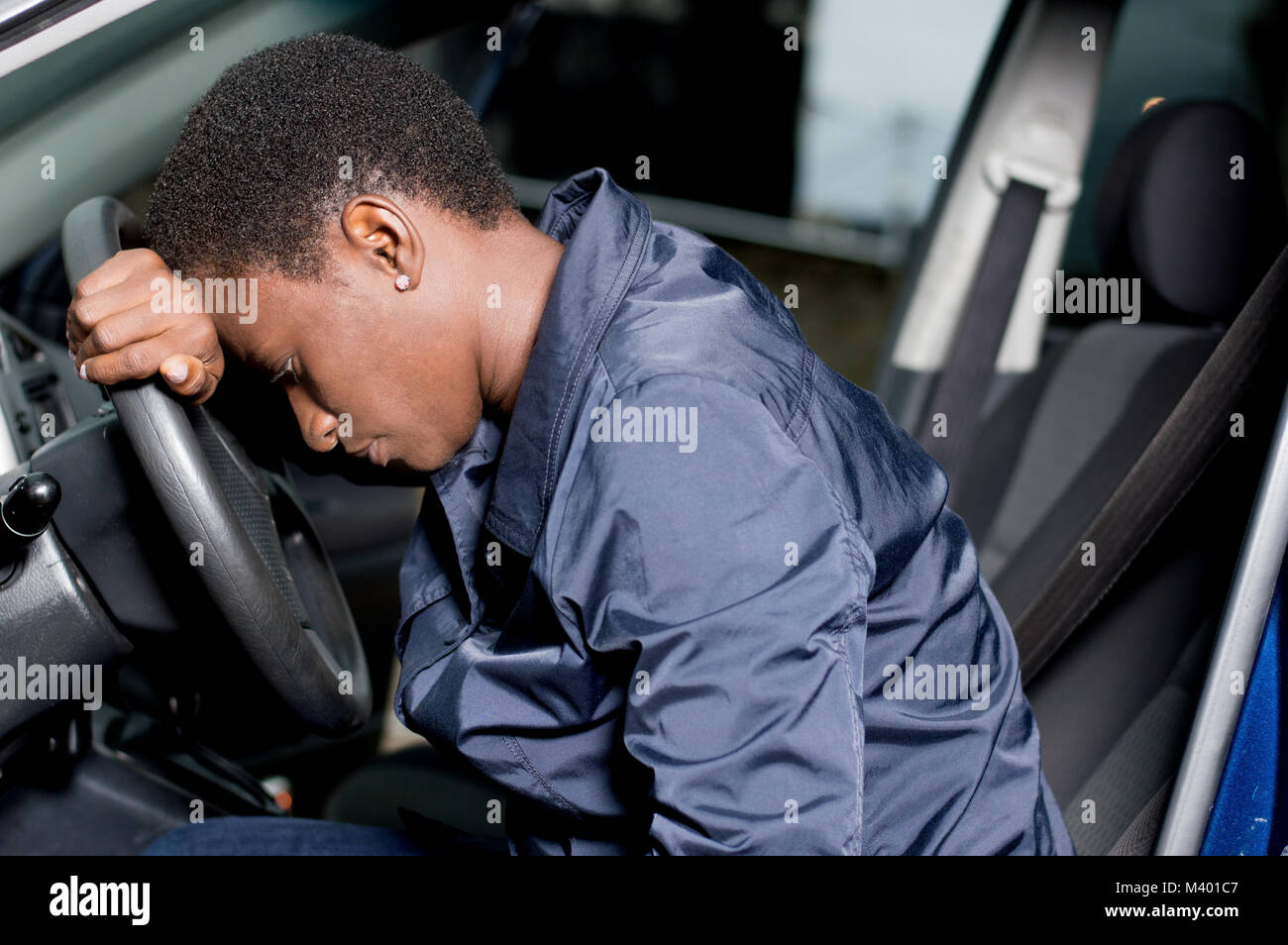 Young woman mechanic sitting at the wheel of a car, head on the wheel and pensive. - Stock Image