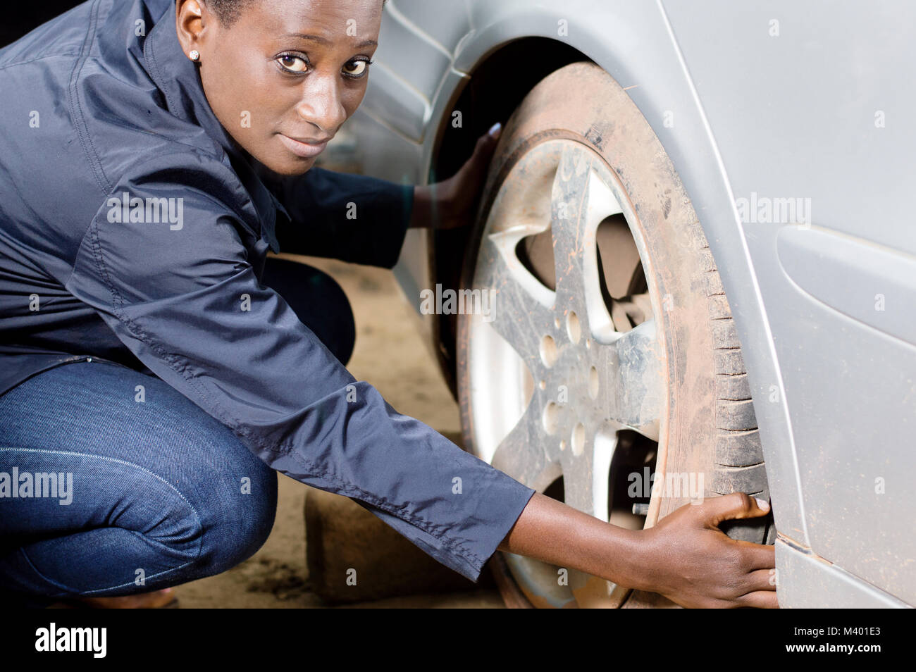 Young woman mechanic squatting near a car removes her tire. - Stock Image