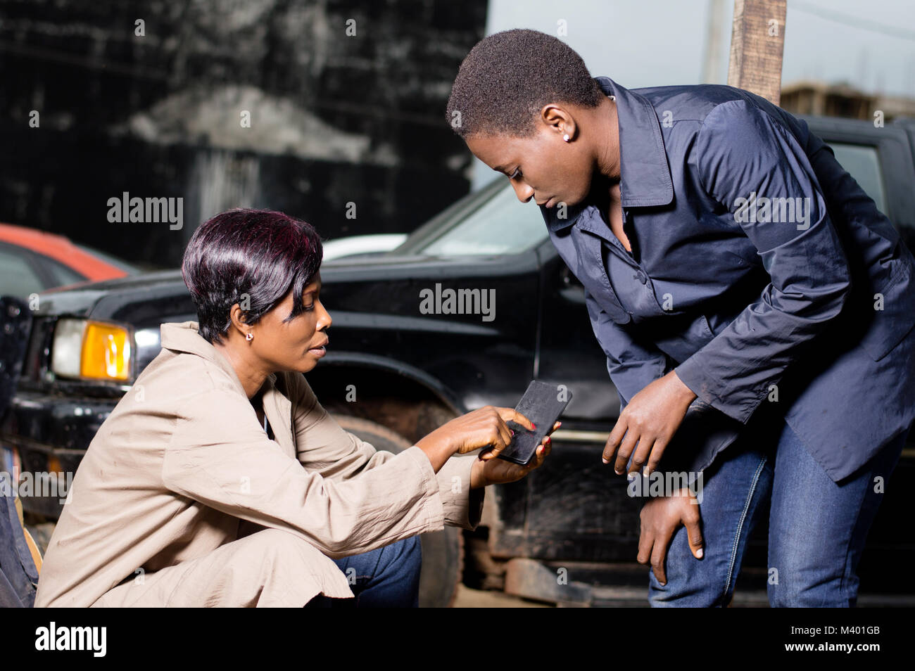 Young woman shows a room exam room she wants for her car to her mechanic in her phone. - Stock Image