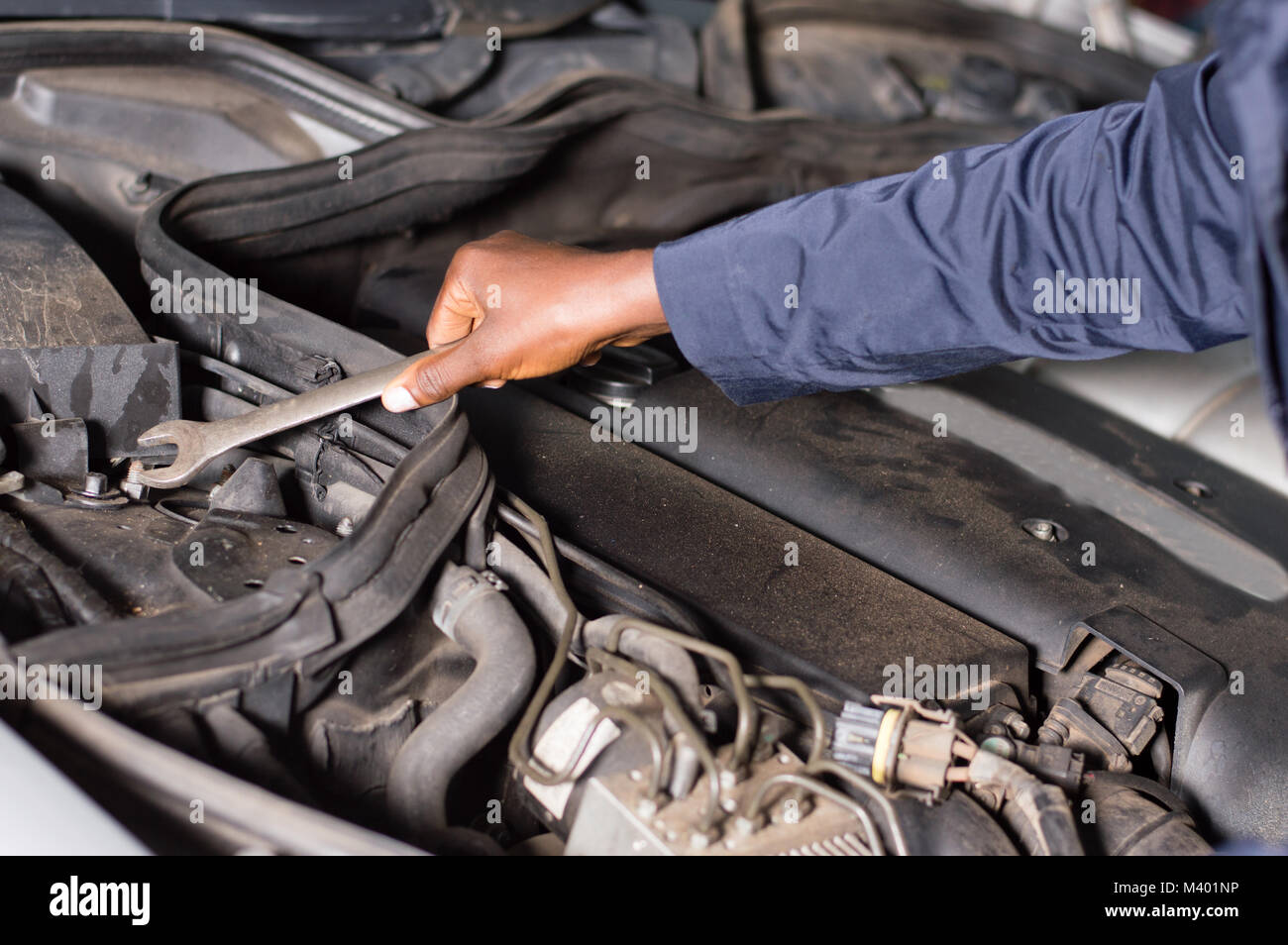 Close-up of a hand holding a key on the engine of a broken car. - Stock Image