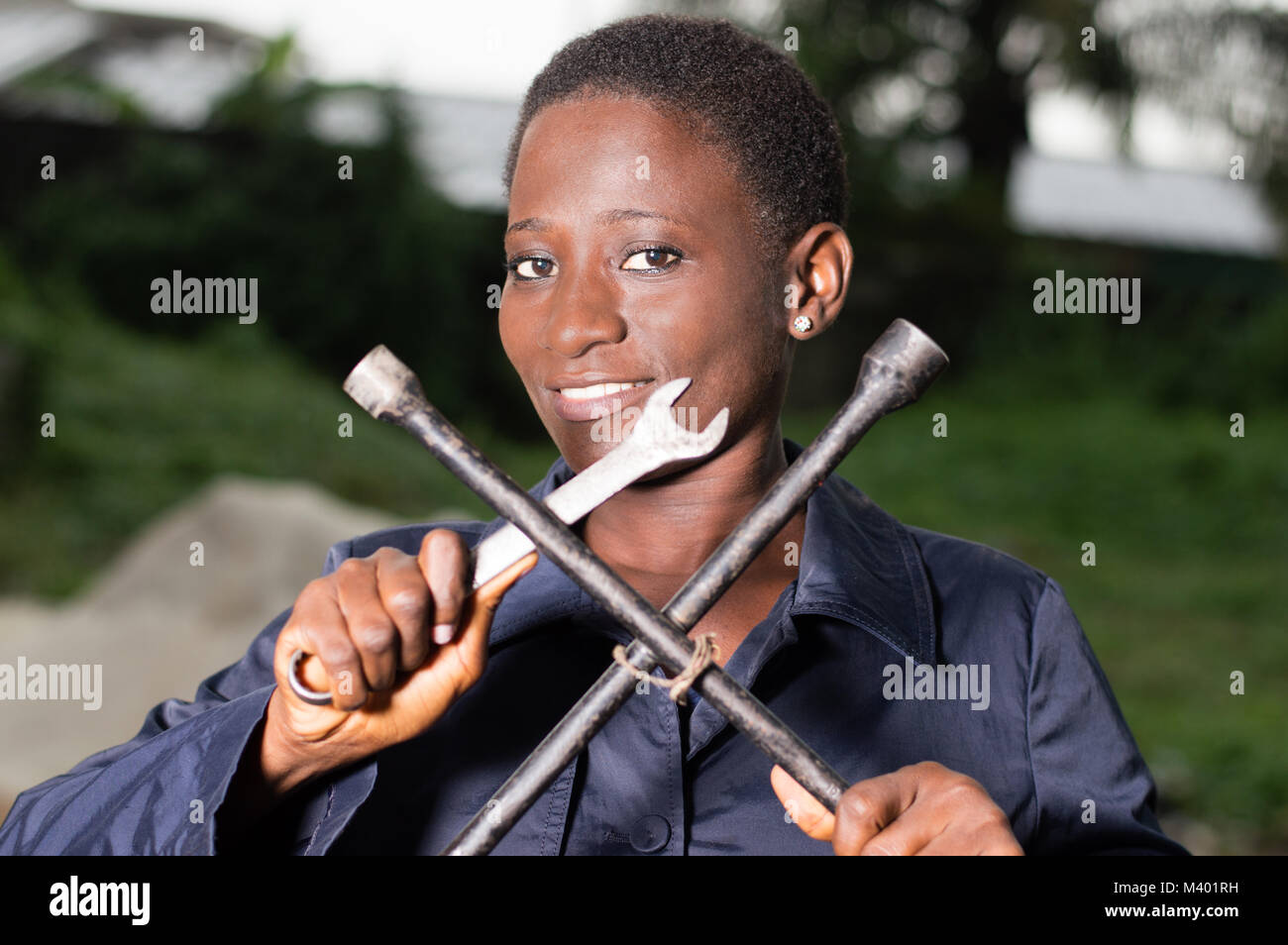 Young smiling mechanic showing her tools in her outdoor studio. - Stock Image