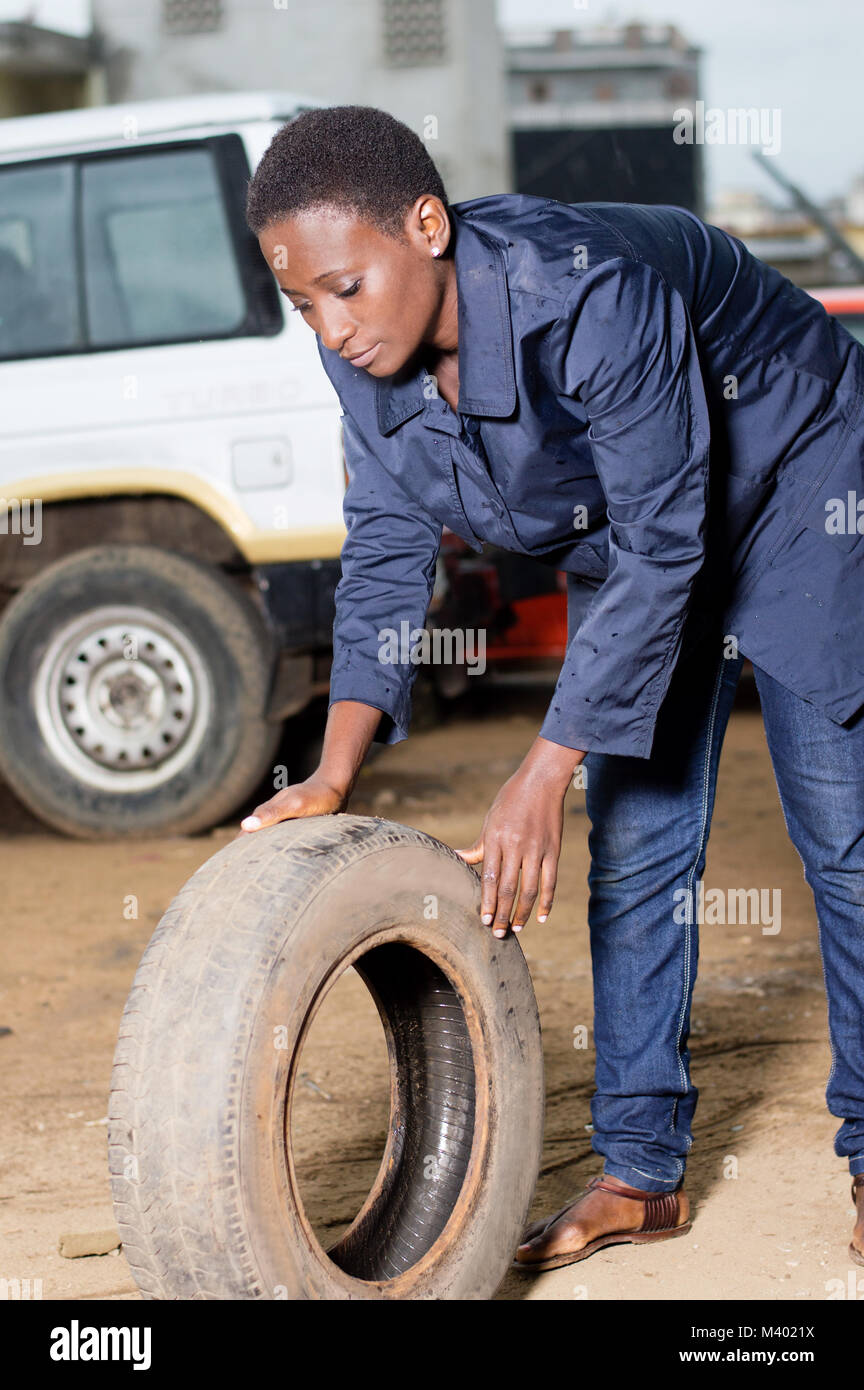 Young female mechanic holds a backup tire for spare in a car workshop. - Stock Image