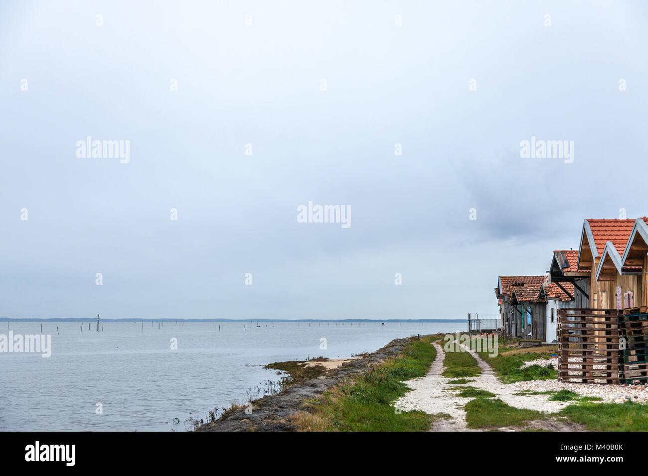 Oyster farmers huts near the Atlantic ocean during a cloudy rainy afternoon on Arachon Bay (Bassin d'Arcachon) - Stock Image