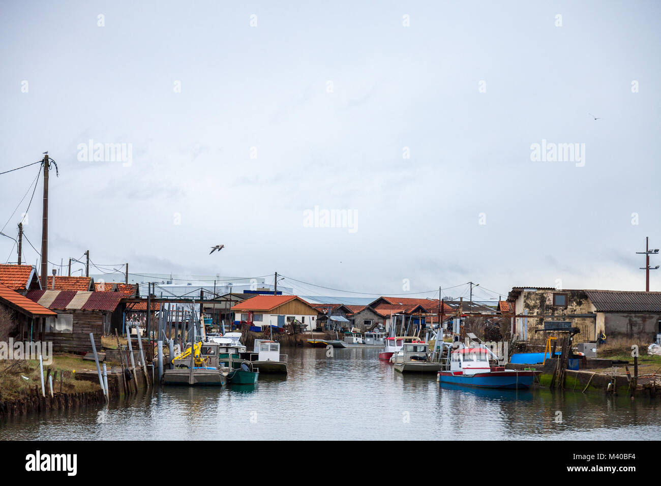 Oyster farmers huts in Gujan Mestras port on the Atlantic ocean during a cloudy rainy afternoon on Arachon Bay (Bassin - Stock Image