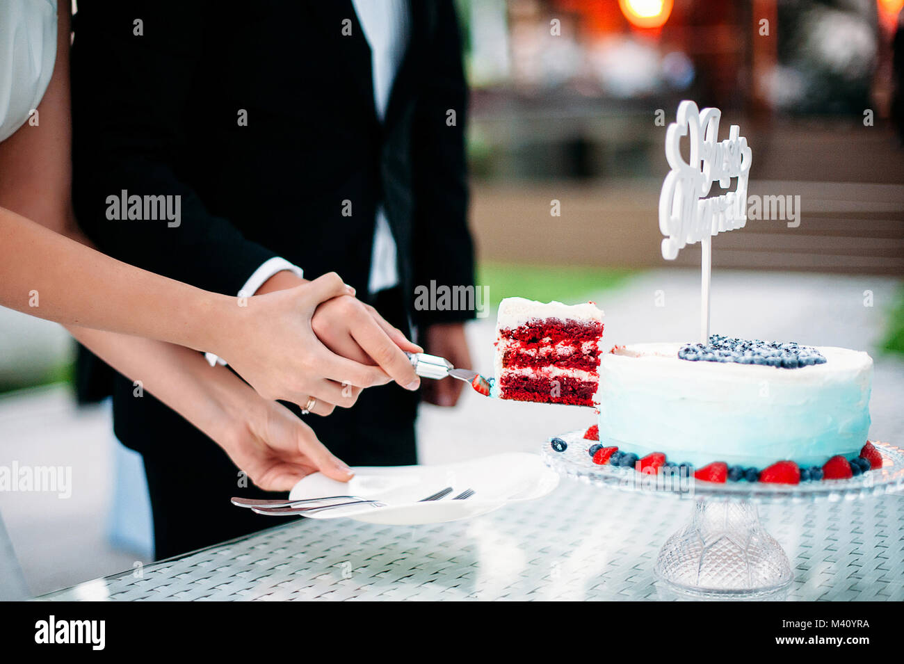 The newlyweds cut a piece of wedding cake Red Velvet. White and blue gradient cake with sign Just Married, decoration - Stock Image