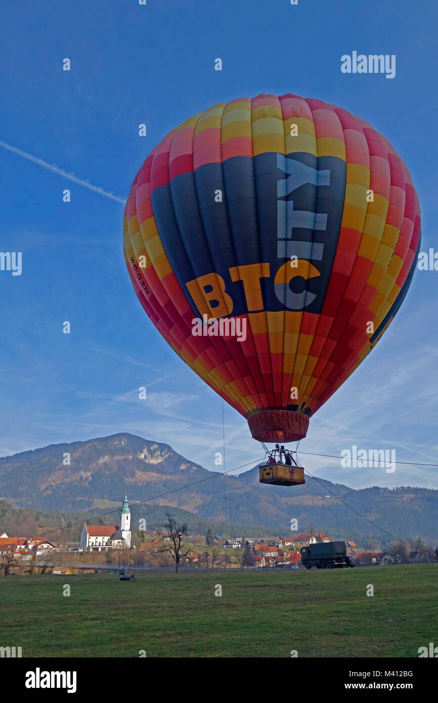 Hot air balloon soars over field and town Ljubno ob Savinji in background. Slovenia. - Stock Image