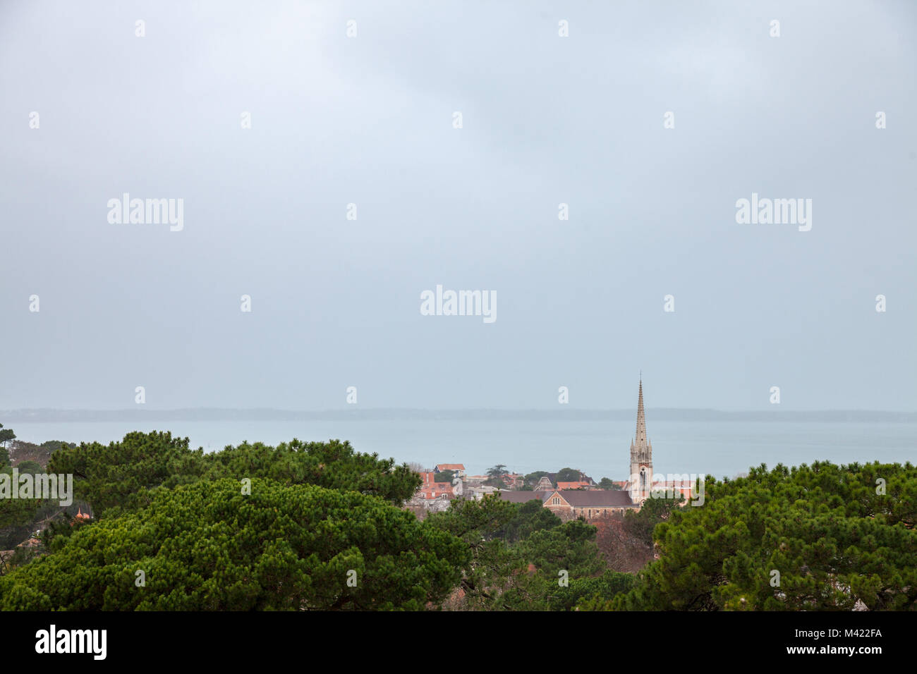 Aerial view of Arcachon, France, during a storm on a cloudy rainy day, witht the Notre Dame basilica in front. Located - Stock Image