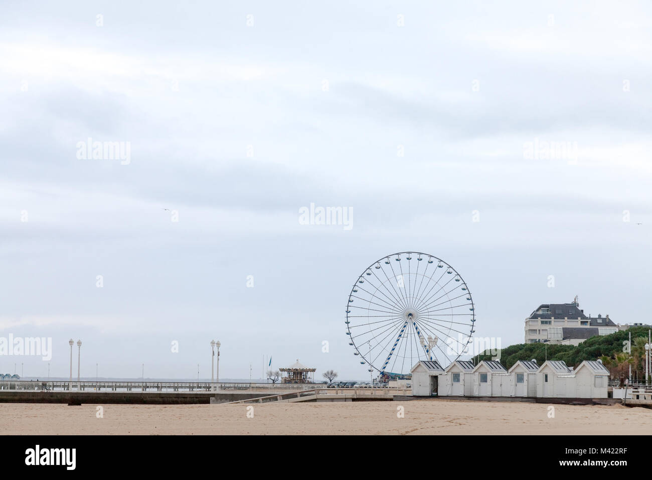 Arcachon ferris wheel on the main pier (Jetee) during a cloudy winter afternoon. The beach and some merchants huts - Stock Image