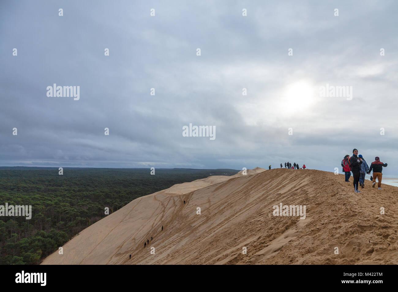 PILAT, FRANCE - DECEMBER 28, 2017: Tourists climbing the Pilat Dune (Dune du Pilat) during a cloudy afternoon. Pilat, - Stock Image