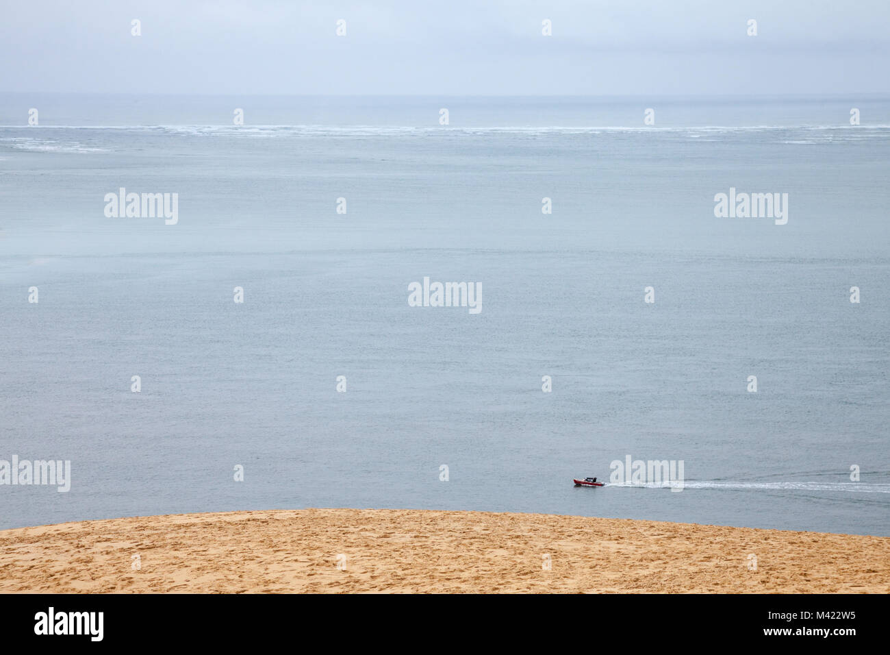 Boat sailing on the Atlantic ocean during a rain story under a cloudy sky passing next to the Pyla Dune. Pyla, or - Stock Image