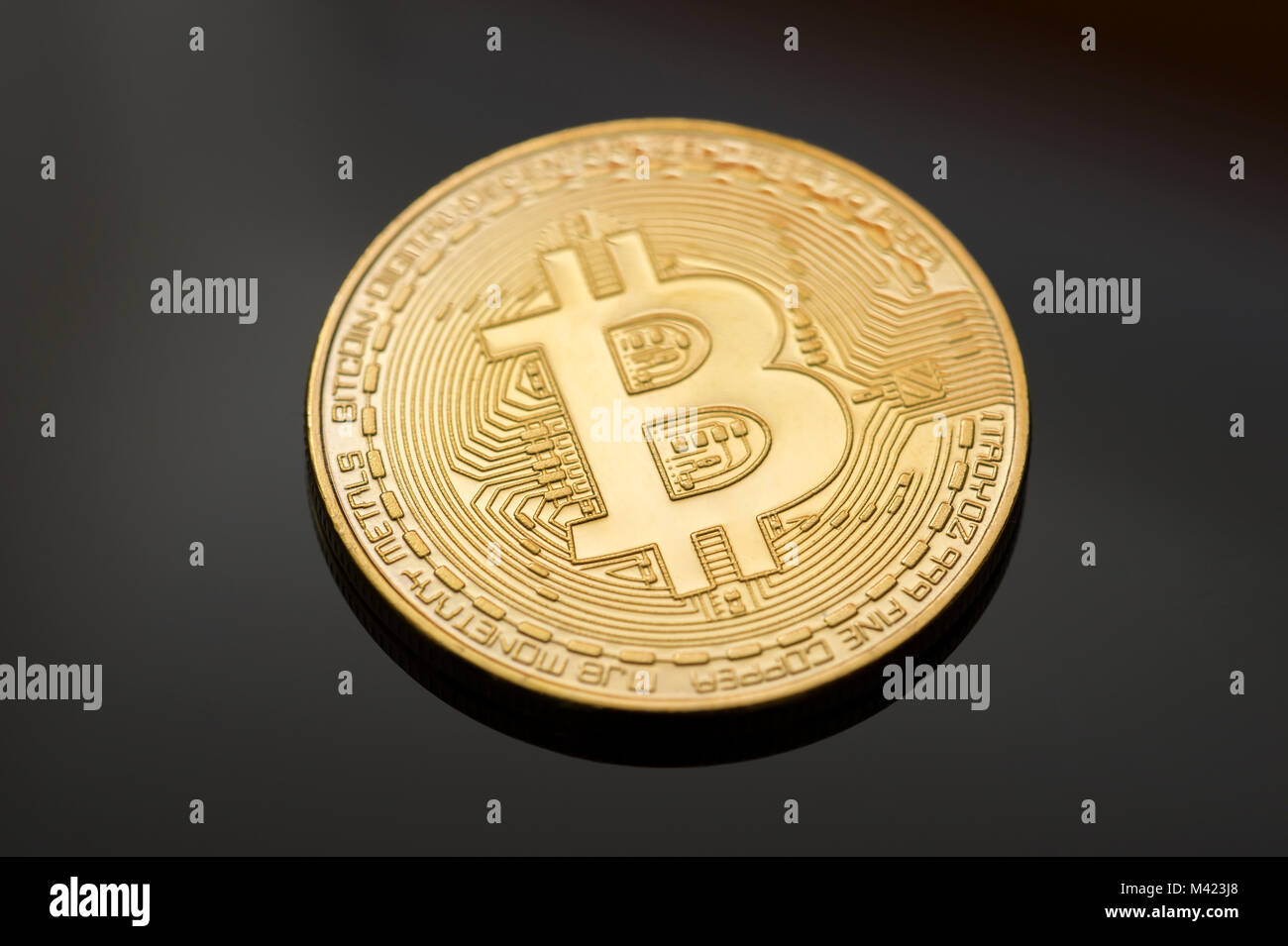 A single Gold Bitcoin on a black background. One of many digital or cryptocurrencies that use blockchain technology - Stock Image