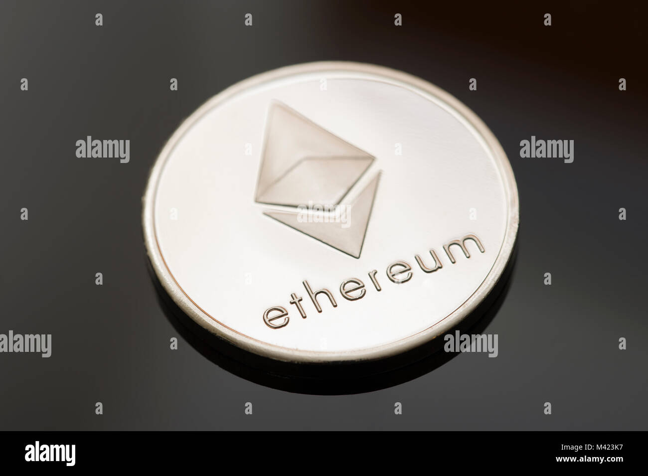 A single Ethereum (Ether) token or coin on a black background. One of many digital or cryptocurrencies that use - Stock Image