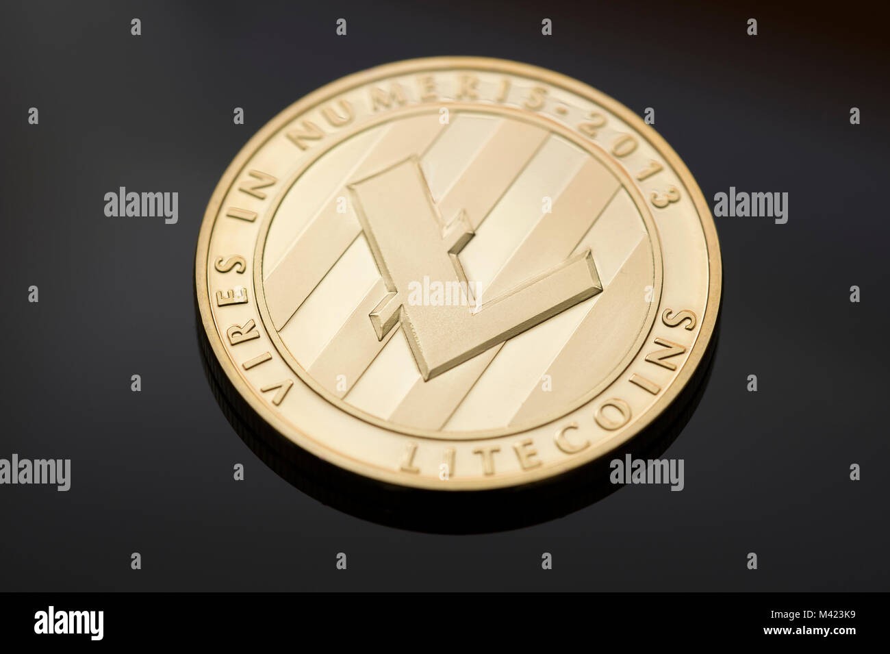 A single Litecoin on a black background. One of many digital or cryptocurrencies that use blockchain technology - Stock Image