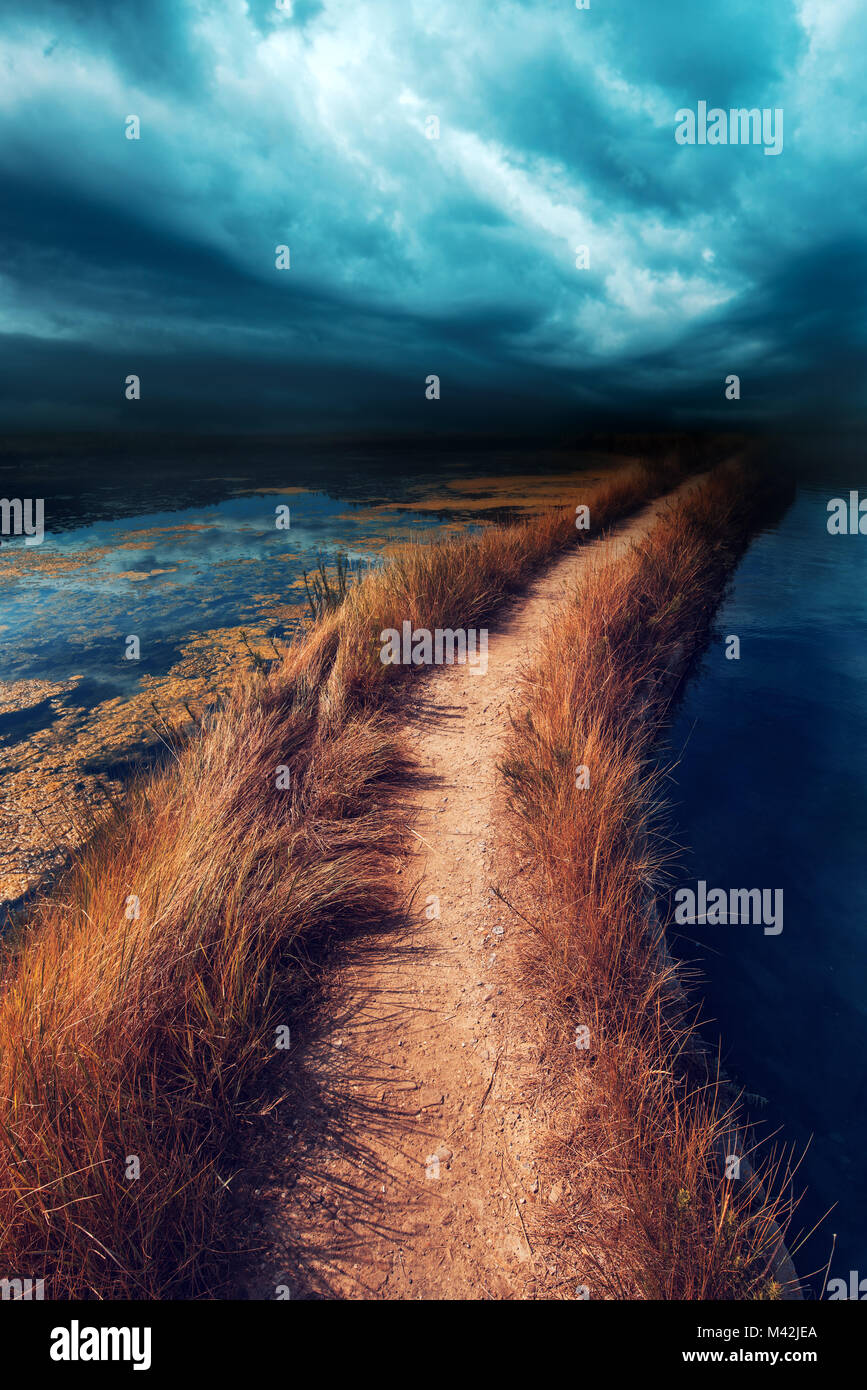 Uncertainty, doubt and insecurity in the future. Risky footpath road through water vanishing in distance, dark stormy - Stock Image