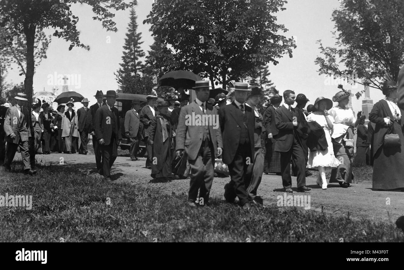 Mourners leave the cemetery after a funeral, ca. 1910. - Stock Image
