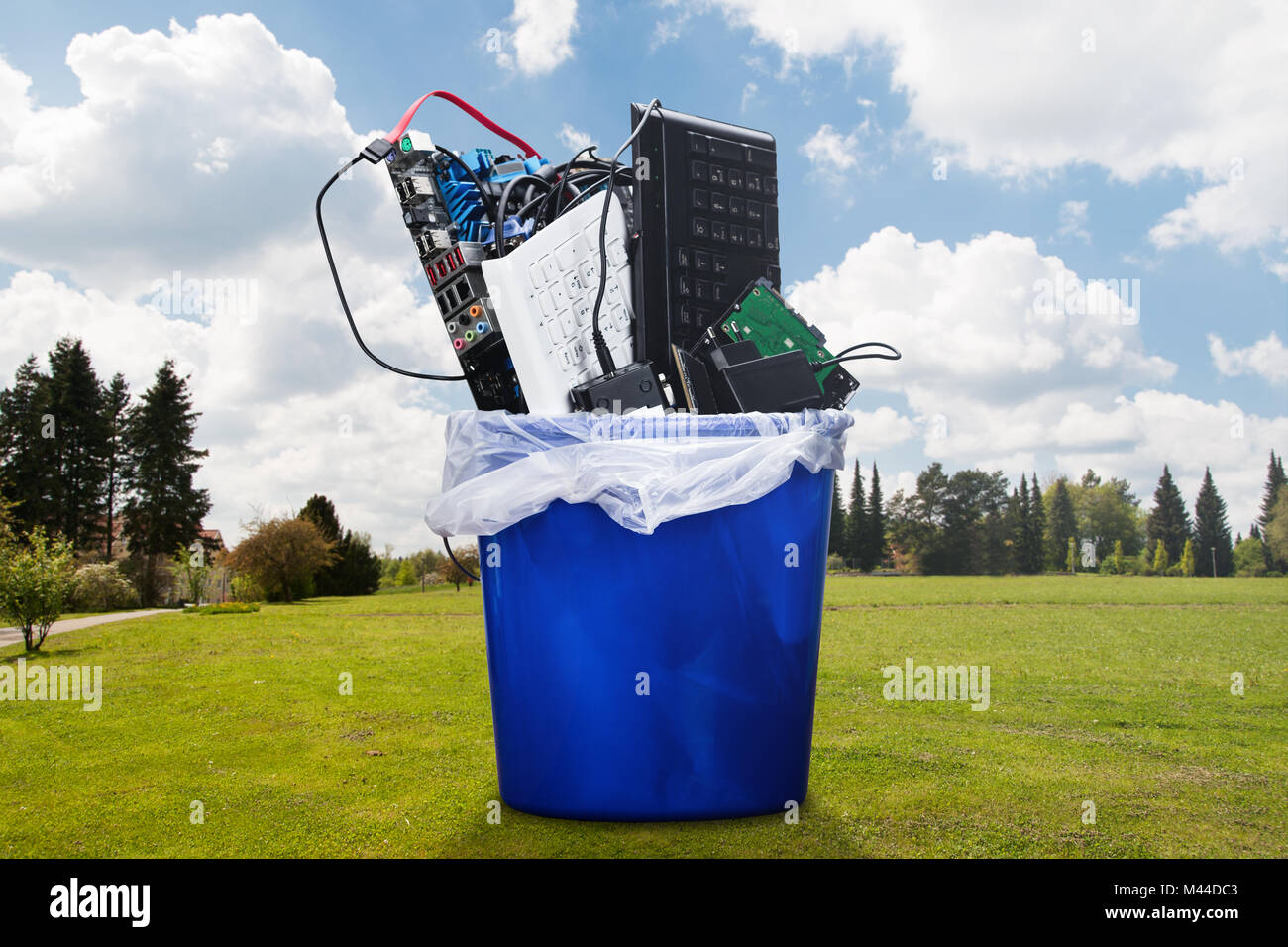 Damaged Hardware Equipment In Blue Dustbin On Lawn - Stock Image
