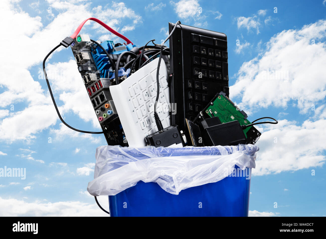 Close-up Of Damaged Hardware Equipment In Blue Dustbin Against Sky - Stock Image