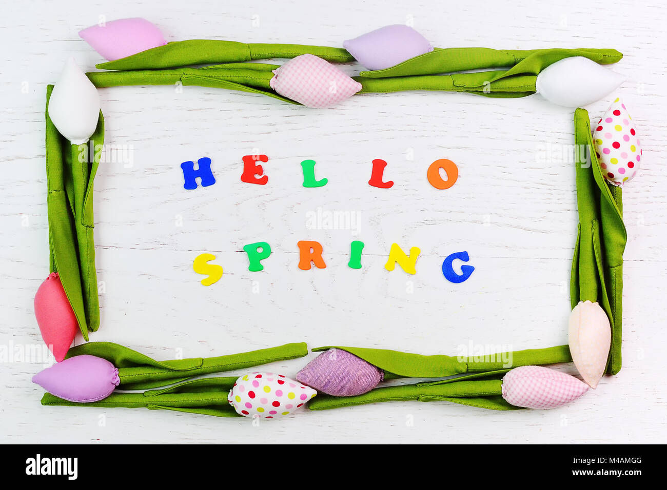 an inscription in colored letters hello spring inside the frame of tulip toy flowers - Stock Image