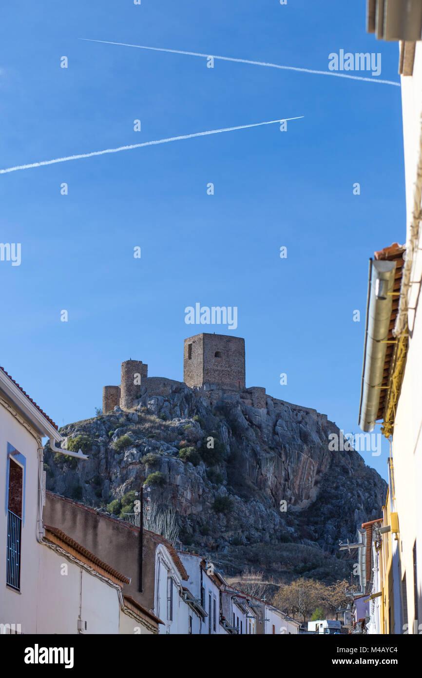 Outcrop rocky hill with Castle of Belmez, Cordoba, Spain. Jet contrails over blue sky - Stock Image