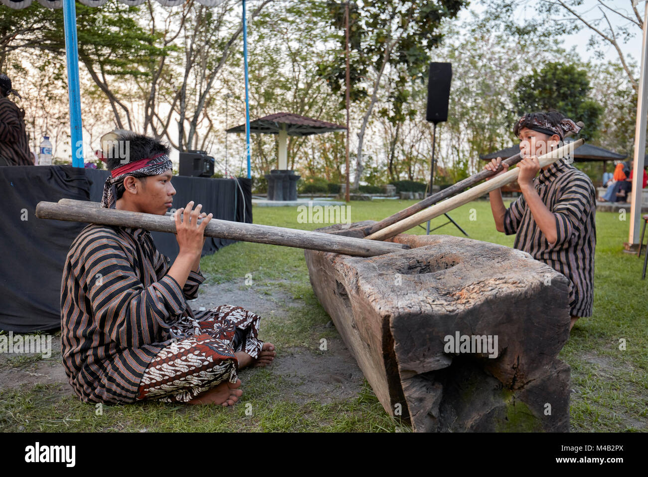Young Indonesian musicians playing on massive woodblock drum. Ratu Boko Palace compound, Special Region of Yogyakarta, - Stock Image