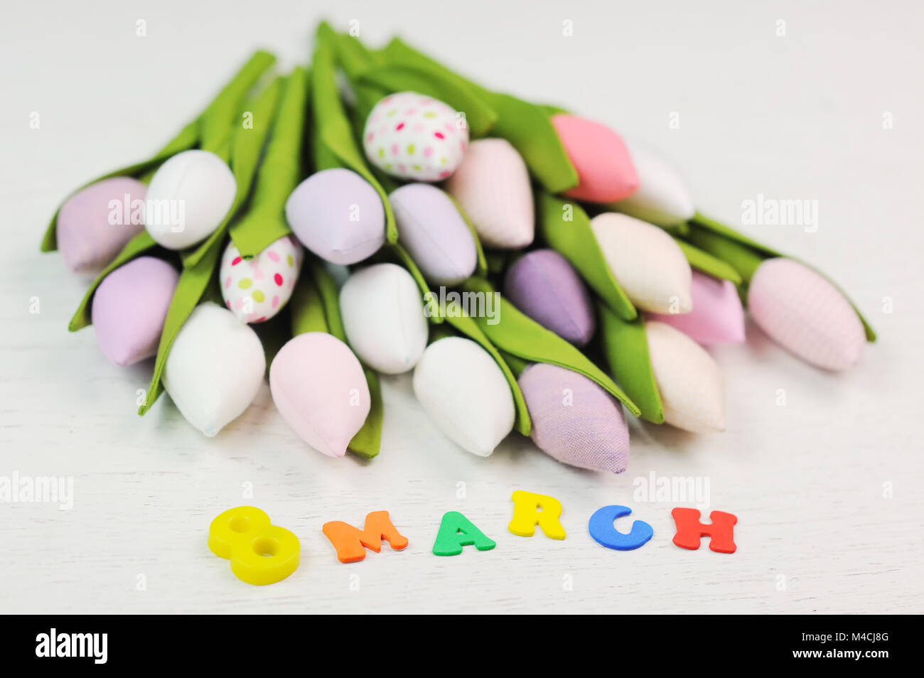 inscription from color letters - March 8 against a background of toy tulips flowers  - Stock Image