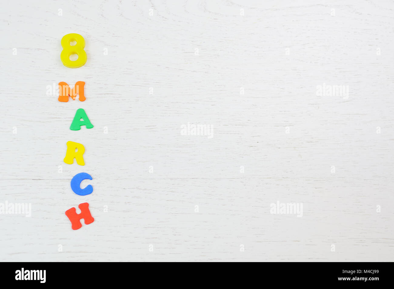 inscription on March 8 from colored letters on a white wooden background - Stock Image