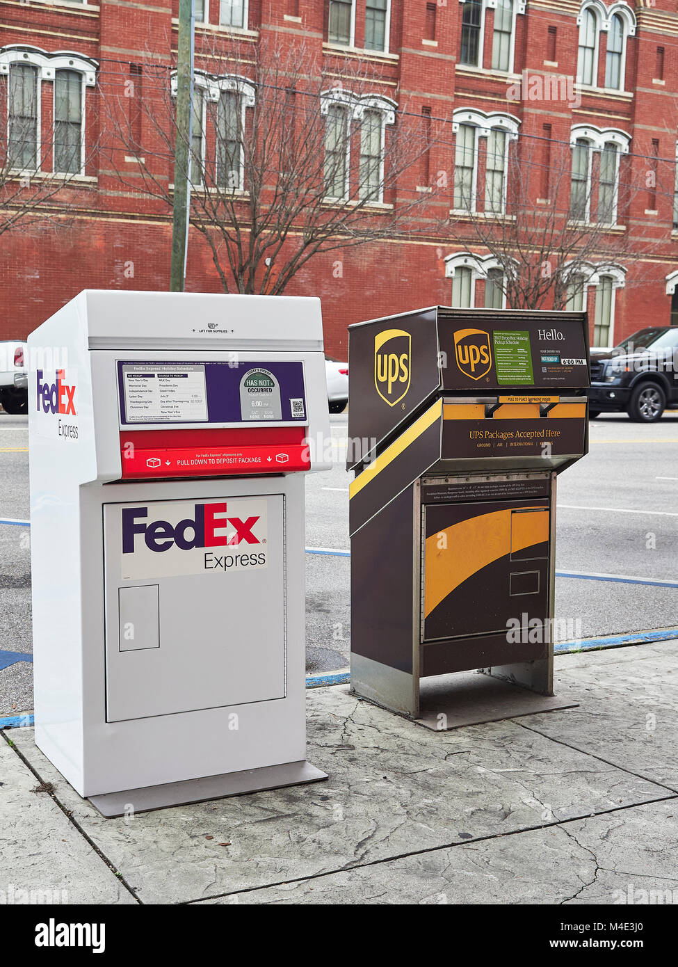 FedEx and UPS collection or drop off boxes sitting on the edge of the sidewalk, curb side, in downtown Montgomery, - Stock Image