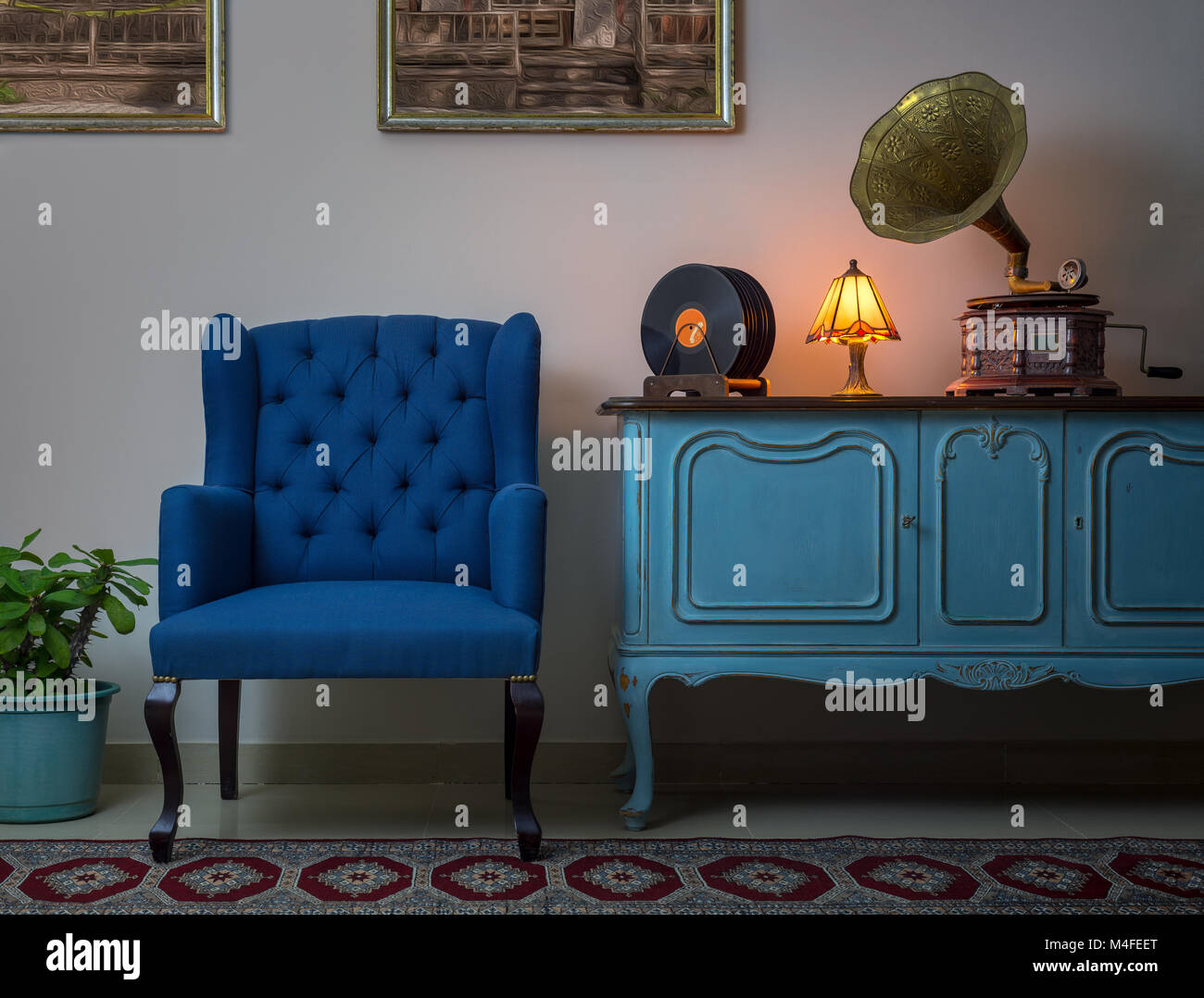 Interior shot of blue armchair, vintage wooden light blue sideboard, lighted antique table lamp, old phonograph - Stock Image