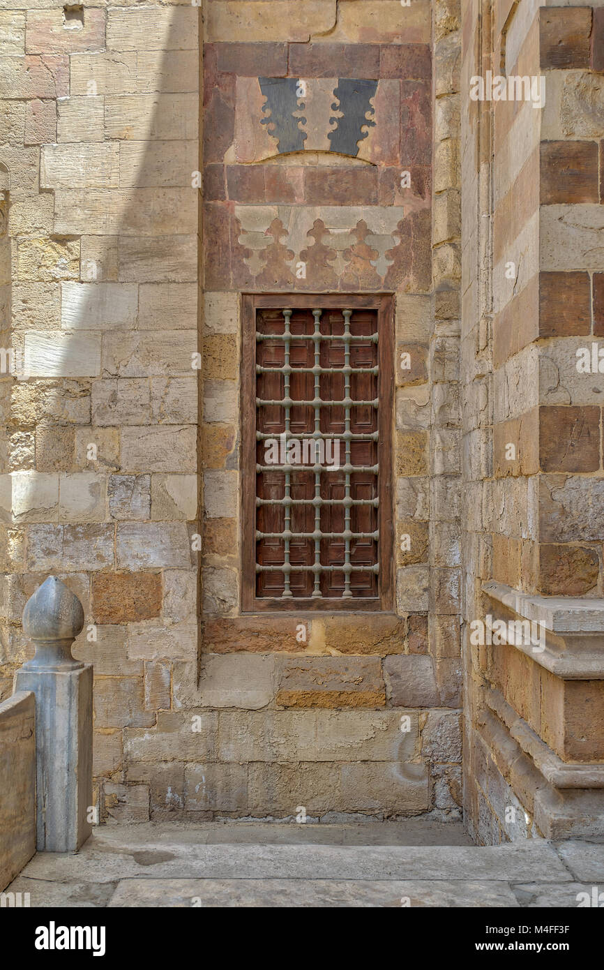 Grunge wooden aged window with iron bars on exterior stone bricks wall of Amir Aqsunqur Mosque (Blue Mosque), Medieval - Stock Image
