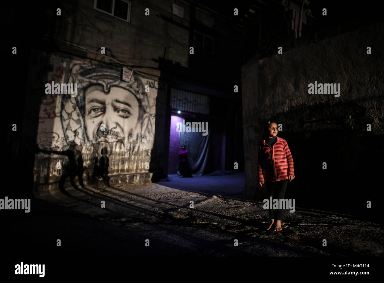 Palestinian girl stands next to a graffiti of late Palestinian leader Yasser Arafat in a dark street during apower - Stock Image