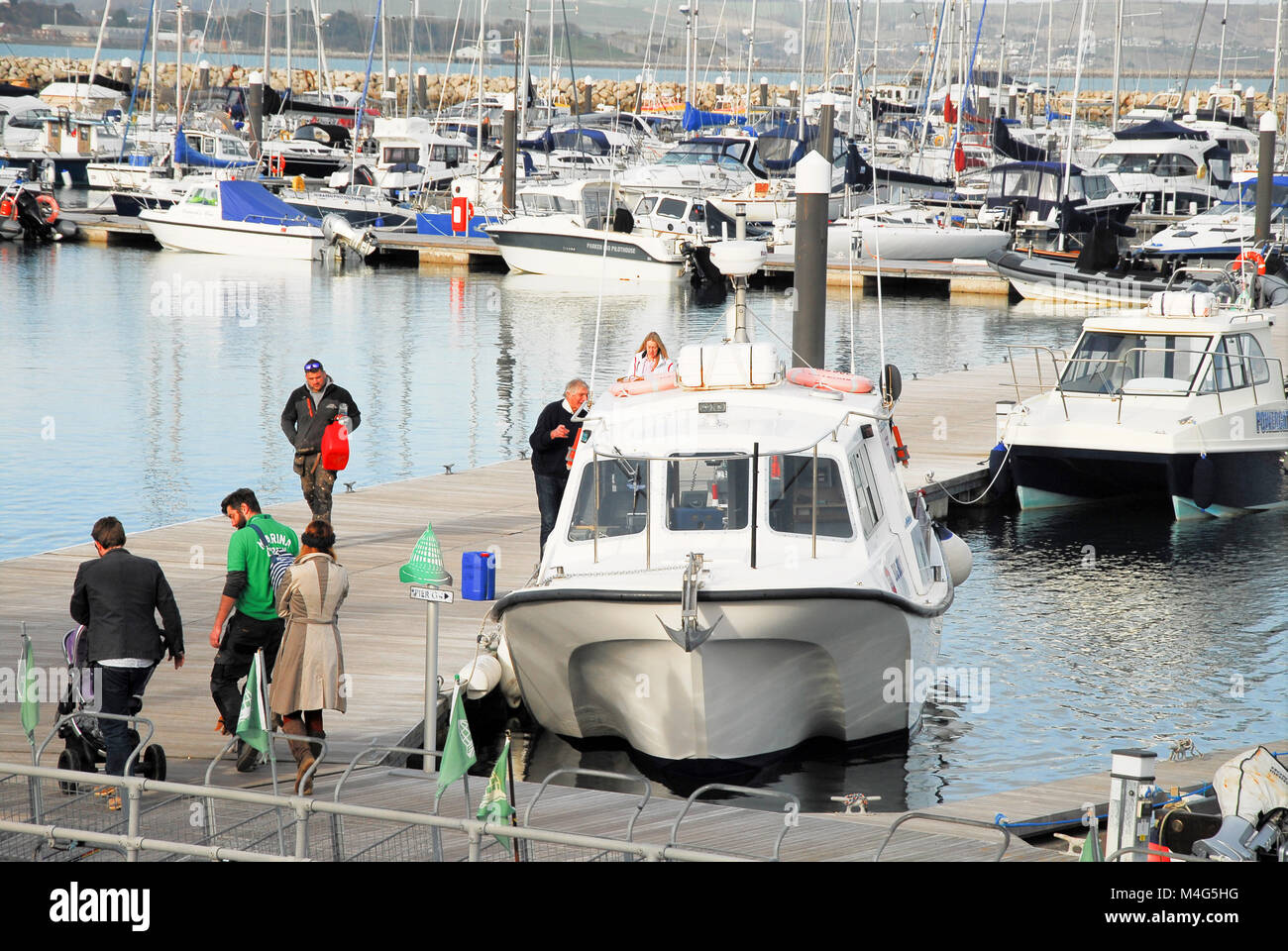 Portland, Dorset. 16th February 2018. People stroll to their boats on a sunny day in Portland Marina, with a high - Stock Image