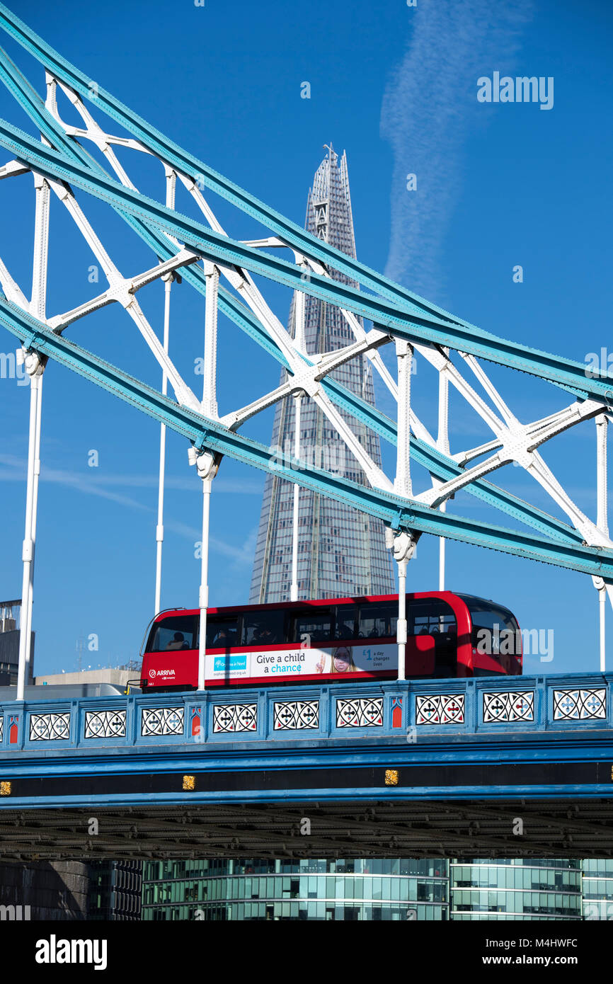 Red London bus crossing Tower Bridge with the Shard in the background, London, England, UK - Stock Image