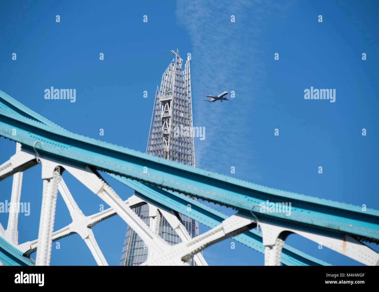 The Shard in London, England, UK, viewed from Tower Bridge with a passenger plane flying nearby - Stock Image