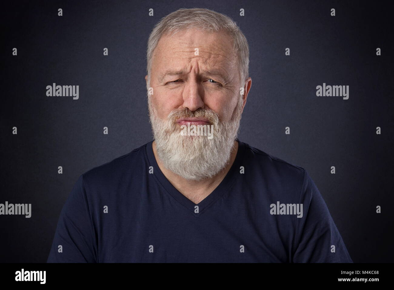 A 60 year old man with gray beard posing spoiled grimace in the studio - Stock Image