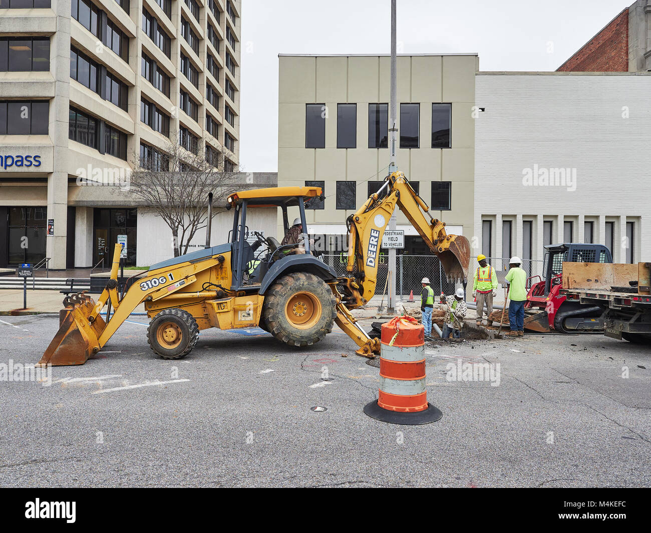 Utility work being done under a paved city street involving a back hoe front loader and several workers in Montgomery - Stock Image