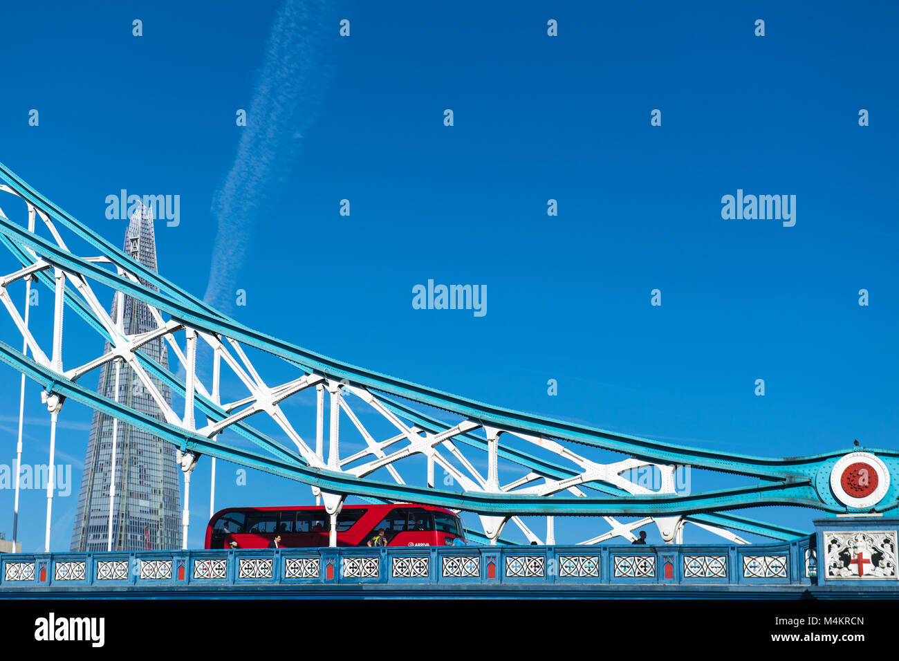 Red double decker bus driving on Tower Bridge in London, England, UK - Stock Image