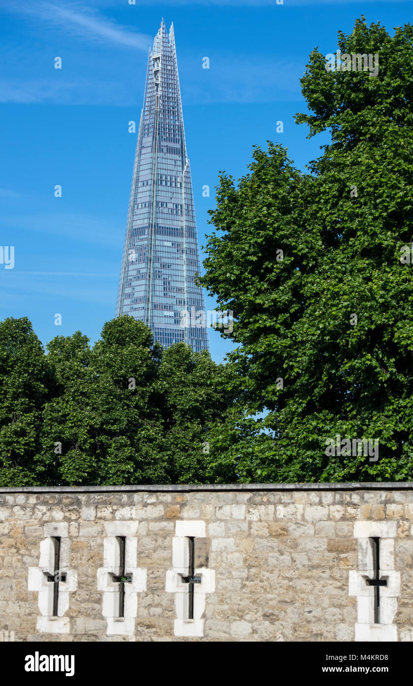 The Shard in London, with the walls of the Tower of London in the foreground, England, UK - Stock Image