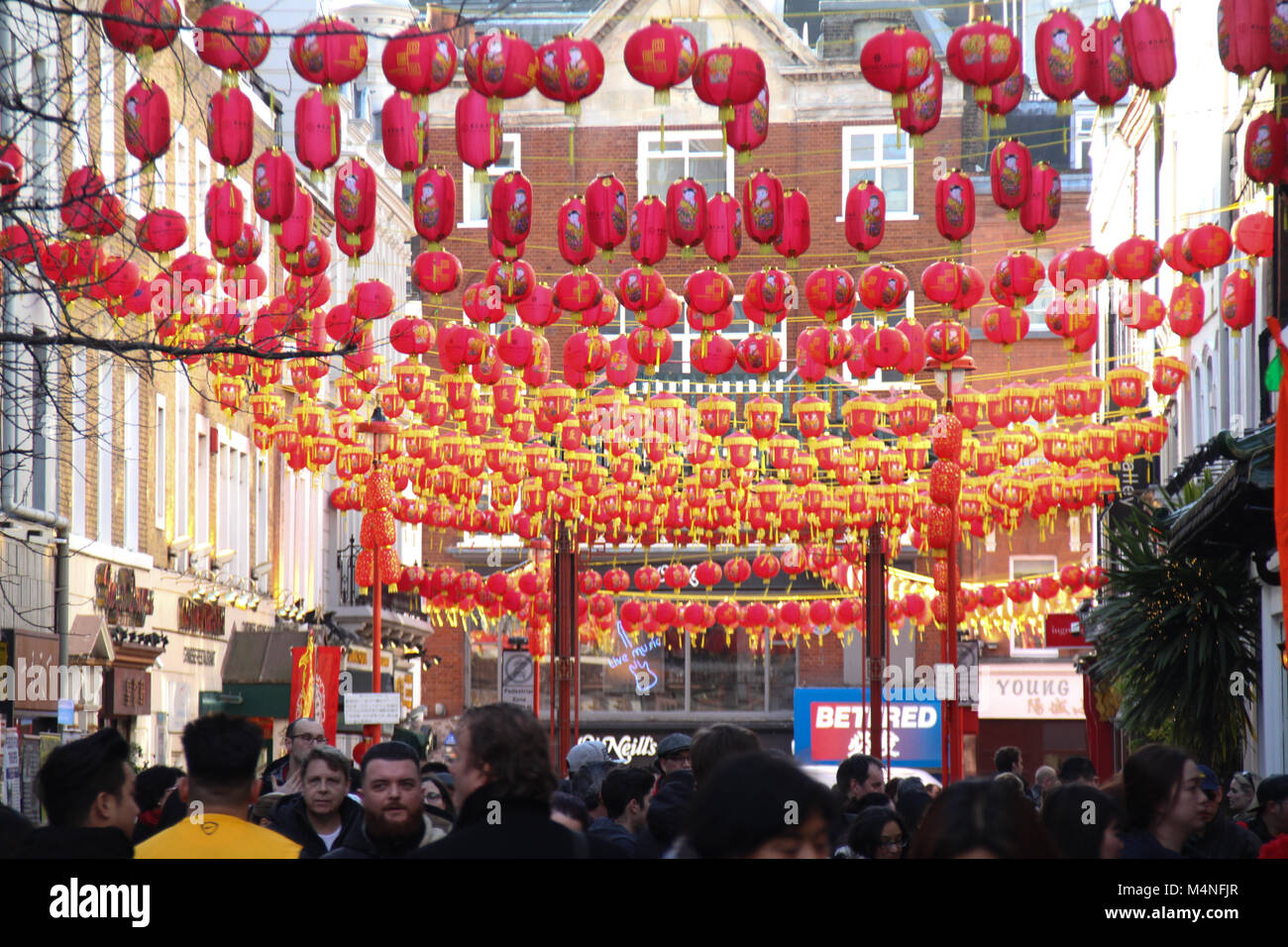London, UK. 17th Feb, 2018. Londoners seen walkinb below Chinese lanterns in China Town London on 17 February 2018 - Stock Image