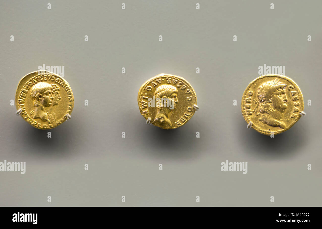 Merida, Spain - December 20th, 2017: Three golden coins of Nero Emperor at National Museum of Roman Art in Merida, - Stock Image
