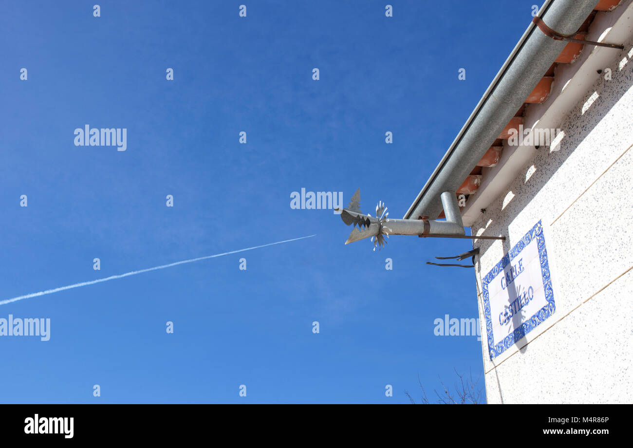 Zinc gutter drainage system dragon shaped and Jet contrail over blue sky. Southern spain - Stock Image